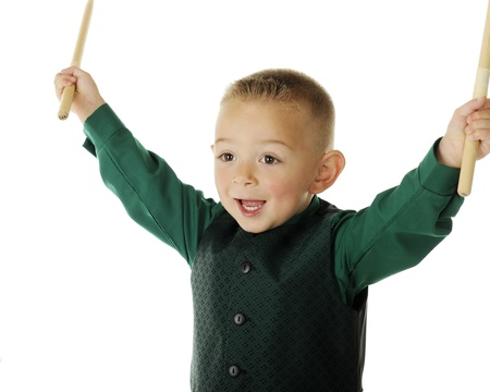 Close-up of a young preschoolder happily raising his drum sticks in victory after performing on the drums.  On a white background.