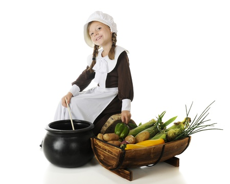 A beautiful elementary pilgrim happily girl sitrring a cauldron with a half- barrel full of vegetables by her side.  On a white background. Stock Photo - 15171774