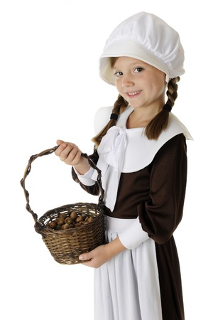 A beautiful elementary Pilgrim displying her basketful of acorns.  On a white background. Stock Photo - 15171786