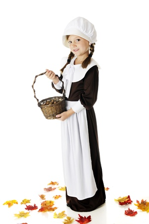 A beautiful elementary Pilgrim girl holding a basketfull of the acorns she's collected.  She's surrounded by colorful fall leaves.  On a white background. Stock Photo - 15171777