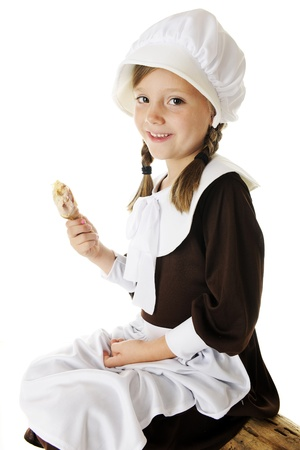 An attractive elementary Pilgrim girl enjoying a small drumstick as she sits on a log.  On a white background.