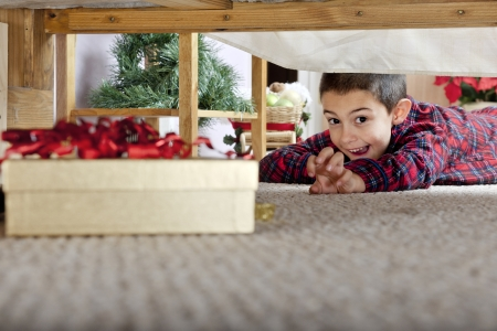 A young elementary boy delighted at seeing a boxed gift under his parents bed.