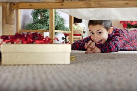 finding: Un muchacho joven elemental encantado al ver una caja de regalo bajo la cama de sus padres.