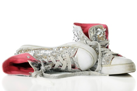 Close-up image of used girls sparkly sneakers with bright pink linings.  On a white background. Stock Photo