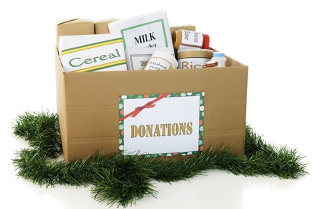 A large corrugated box filled with containers of donated food, surrounded by green Christmas garland.  On a white background. photo
