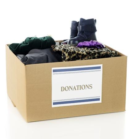 """ropa de invierno: Una gran caja de cart�n ondulado con una """"Donaciones"""" signo y lleno de una gran variedad de ropa de abrigo de invierno,. En un fondo blanco."""
