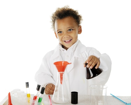 An adorable preschool chemist happily preparing to pour a dark liquid from one glass flask into another.