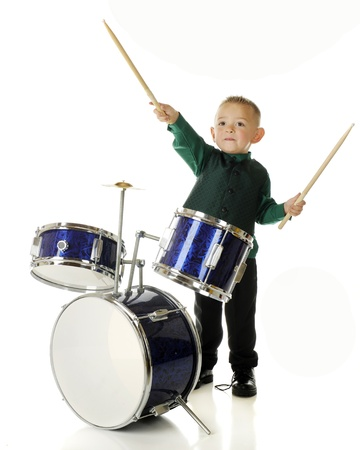 cymbol: An adorable preschooler behind a drum set.  Hes pretending to conduct an orchestra with his drum sticks.  On a white background. Stock Photo