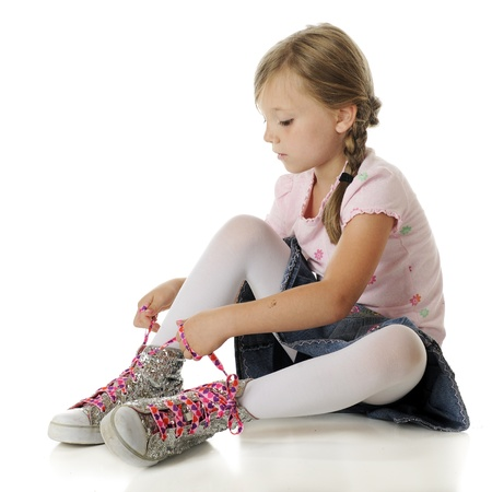 A pretty elementary girl tying heart-covered, neon pink laces on overs zied sparkly high-top sneakers.  On a white background.