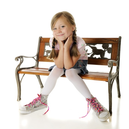 oversized: A pretty elementary girl sitting on a bench, delighted with her over-sized, high-top, sparkly sneakers.  On a white background. Stock Photo