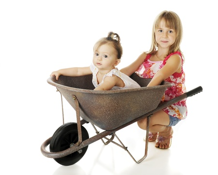 Two sisters with a wheelbarrow -- an adorable baby inside, her attractive elementary sister squatting behind it.  On a white background. photo