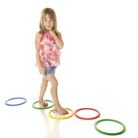 A young elementary girl walking a path of colorful rings.  On a white background. Stock Photo