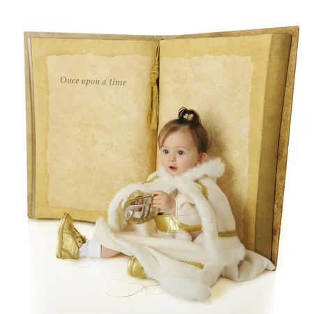 An adorable baby 'Snow Princess' sitting in front of a giant book opened to a page that says 'Once Upon a Time...'.  The rest is left blank for your text.  On a white background. photo
