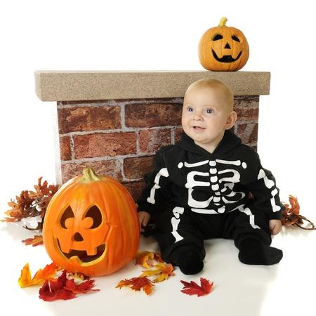 zucche halloween: Un scheletro di bambino adorabile seduta da un muro tra le zucche di Halloween e foglie colorate su uno sfondo bianco