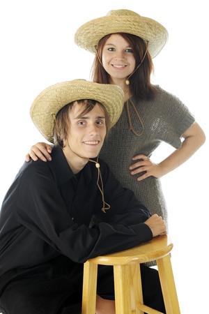 lookalike: Portrait of a happy teenage couple, both wearing look-alike straw hats.  On a white background.