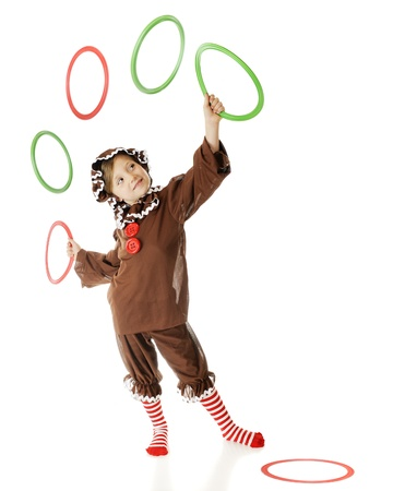 An adorable elementary gingerbread girl, happily juggling Christmas colored rings.  (Motion blur on airborne rings.)  On a white background. Stock Photo - 15335218
