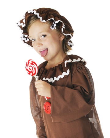gingerbread: A cute elementary gingerbread girl licking a red and while swirrled lollipop.  On a white background.
