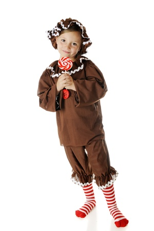 An adorable elementary gingerbread girl, happily holding her red and while swirled lollipop.  On a white background. Stock Photo - 15335221