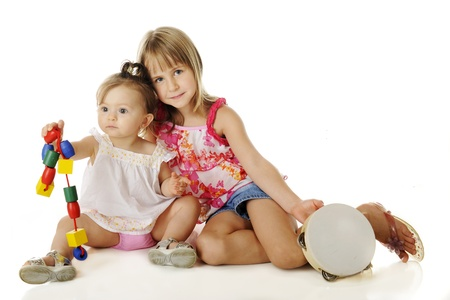 girl in shorts: Young sisters playing together.  The older one stops for a moment to pose with the baby.  On a white background.