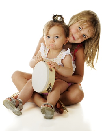 An adorable baby girl sitting on her happy elementary-aged sisters lap.  On a white background.  Stock Photo