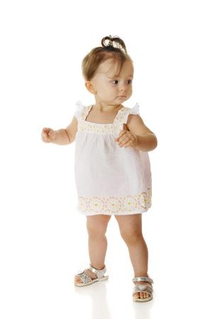 sandalia: Una ni�a adorable mirando hacia atr�s nerviosamente mientras ella da sus primeros pasos lejos de mam�. En un fondo blanco. Foto de archivo