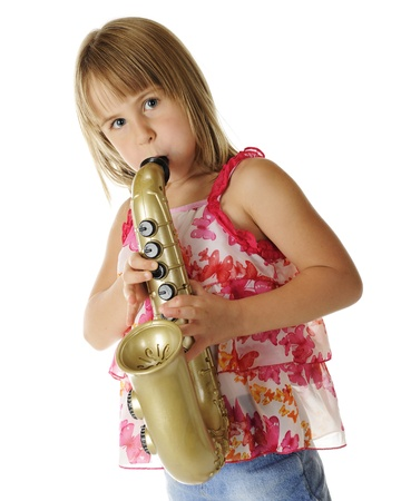 puffed cheeks: A pretty young elementary girl with puffed out cheeks, as she plays a toy saxaphone.  On a white background.