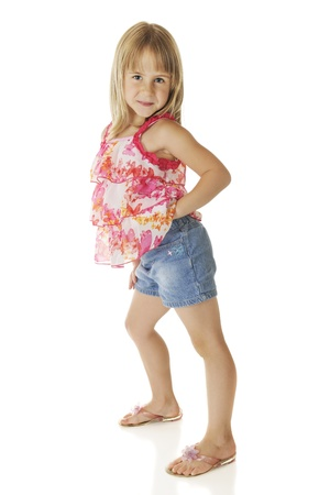 sassy: An adorable elementary girl getting sassy in her frilly top and denim shorts.  On a white background.