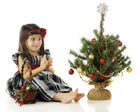 A pretty little preschooler happily putting Christmas bulbs on her own tiny tree.  On a white background. Stock Photo - 15335226