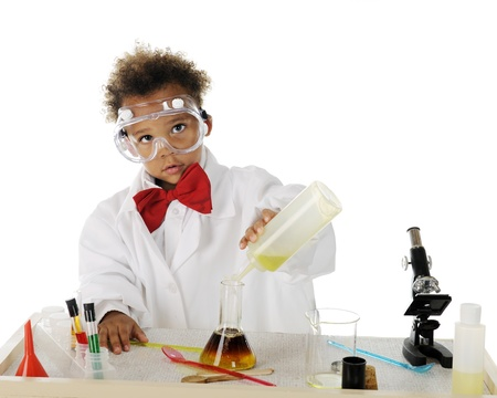 An adorable tot mixing chemicals on his science table.  On a white background.