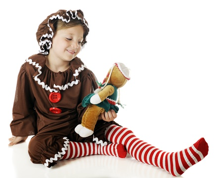 christmas costume: A beautiful elementary gingerbread girl admiring her gingerbread doll.  On a white background. Stock Photo