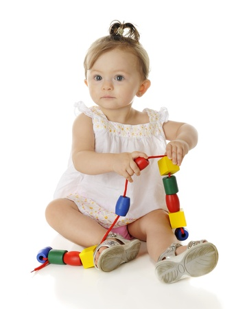 A beautiful baby girl sitting in her sundress and sandals, playing with a string of large, colorful beads.  On a white background.