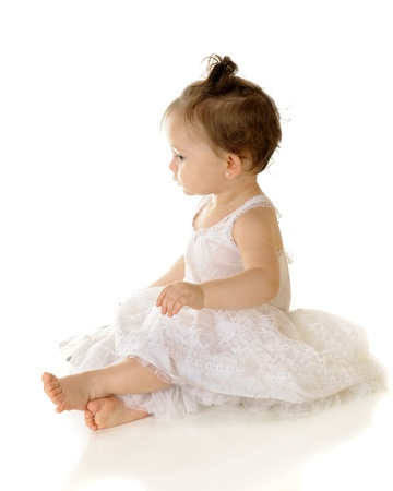 petticoat: High key profile of an adorable baby girll sitting pretty in her petticoat.  On a white background.   Stock Photo