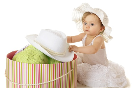 spacey: An adorable baby girl looking spacey in her petticoat as she digs into a large, colorful, filled hat box.  On a white background.