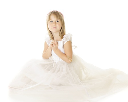 A beautiful elementary girl in white, hands clasped while looking heavenward.  On a white background. Imagens