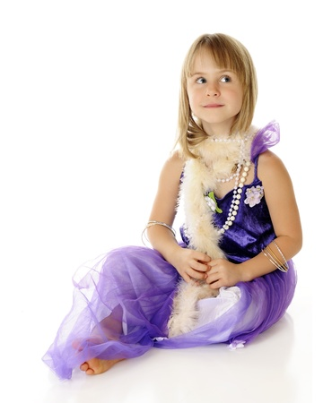 A beautiful young elementary girl looking beautiful in a purple dress, beads and a  pale pink boa.  On a white background. Stock Photo - 15416436