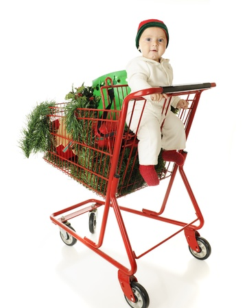 An adorable baby boy happily riding in the child's seat of a red shopping cart filled with Christmas goodies.  On a white background. Stock Photo - 15416445