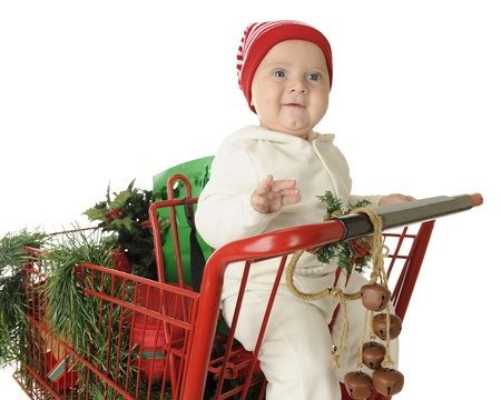 An adorable baby boy happy in the child's seat of a red shopping cart filled with Christmas goodies.  On a white background. Stock Photo - 15416501