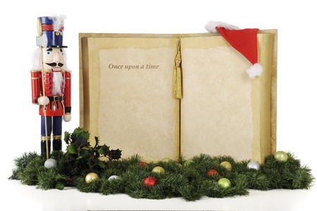 A large opened book with the words 'Once upon a time...'  The remainder left blank for you text.  A tall Christmas nutcracker stands guard on one side with other Christmas ornaments at the base.  On a white background. photo