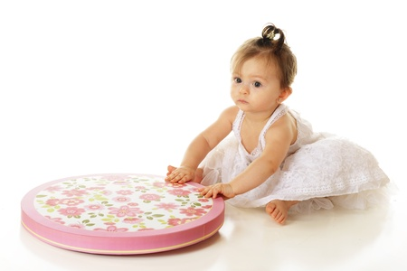 petticoat: An adorable baby girl in her petticoat, picking up a large, flowery hat box lid.  On a white background.