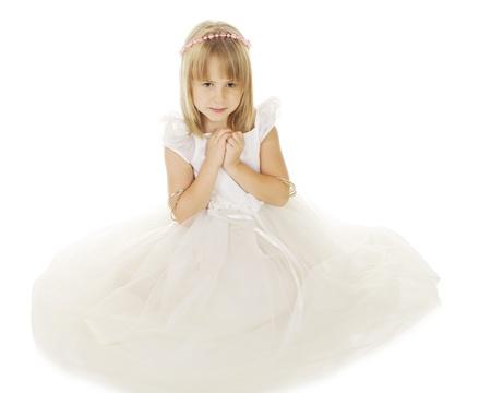 흐르는 흰색 드레스와 분홍색 구슬의 후광에 앉아 아름 다운 작은 소녀. 그녀는 아래로 보이는 그녀의 손을 쥐는됩니다. 흰색 배경에.