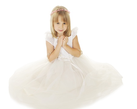 A beautiful little girl sitting in a flowing white dress and a halo of pink beads.  Her hands are clasped as she looks downward.  On a white background.