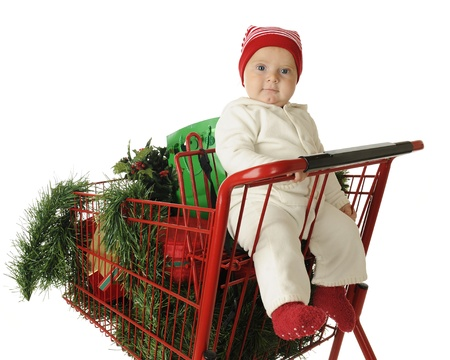 An adorable baby boy in the child's seat of a red shopping cart filled with Christmas cheer.  On a white background. Stock Photo - 15563354