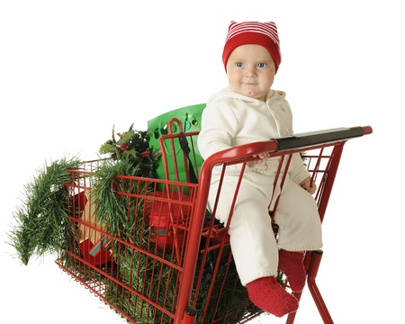 An adorable baby boy happily sitting in the childs seat of a red shopping cart filled with Christmas goodies.  On a white background. photo