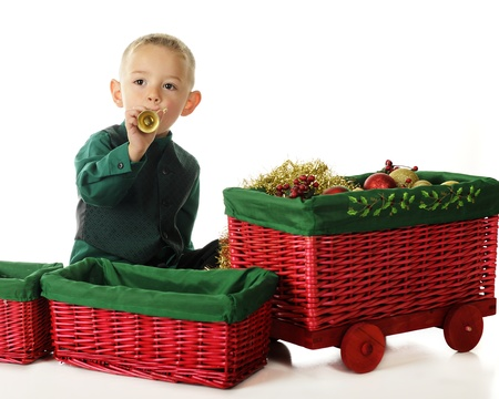 An adorable preschooler blowing a toy trumpet by a red wicker  basket train  filled with Christmas decore   On a white background Stock Photo - 15763283