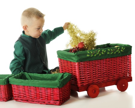 An adorable preschooler pulling garland out from the largest car of a red wicker  basket train    On a white background  Stock Photo - 15763282