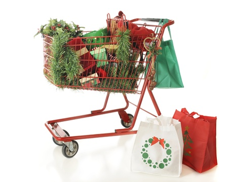 Three reuseable shopping bags and a red shopping basket filled with Christmas shopping goodies   On a white background