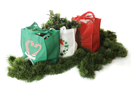 Overhead view of three reuseable shopping bags filled with Christmas goodies and surrounded by green garland   On a white background