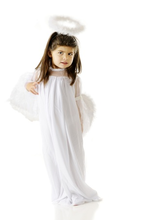 angry angel: A standing little girl looking angry in her angel costume as she Stock Photo