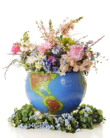 A large topographical globe filled to overflowing with colorful flowers and greenery   On a white background
