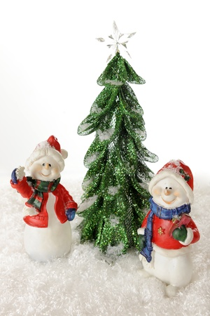 Overhead view of two happy snowmen standing by a tall, start-topped Christmas tree   All are surrounded by snow   On a white background Stock Photo - 15813109